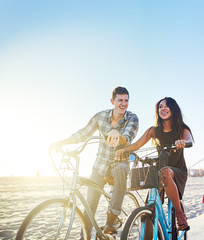 couple on bicycles stopped at sunny california beach
