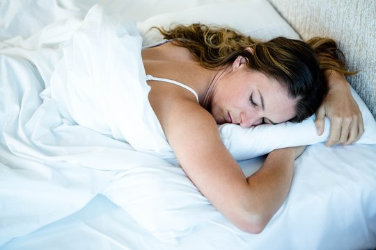 peaceful woman asleep in her bed