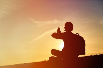 man doing yoga at sunset sky