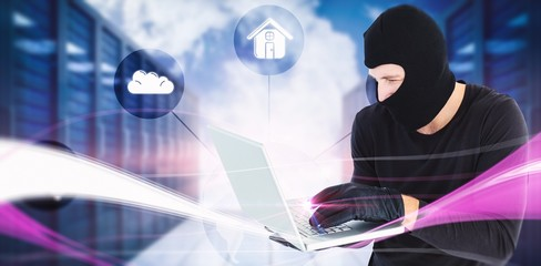 Composite image of focused burglar standing holding laptop
