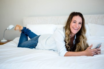 woman lying on her bed on her mobile phone smiling at the camera