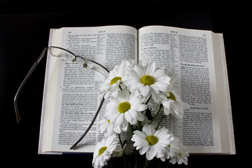 flowers and glasses on the open Gospel on a dark background