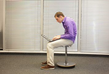 text neck - man in slouching position sitting on pneumatic stool, working with laptop in his office