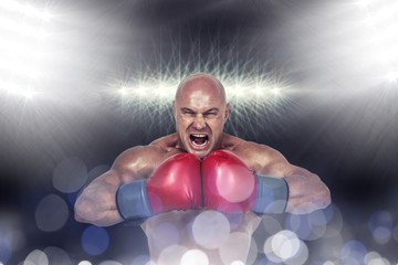 Composite image of aggressive boxer flexing muscles