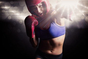 Composite image of female boxer with gloves and headgear
