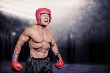 Composite image of angry boxer against black background