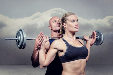 Composite image of trainer helping woman for lifting crossfit