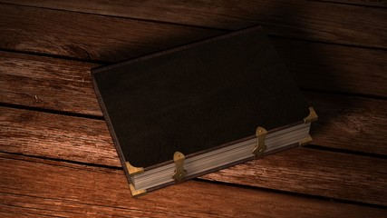 Old leather book on wooden table in candlelight
