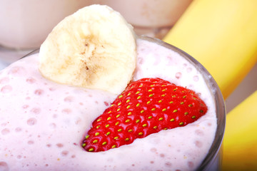 banana and strawberry smoothie on white background