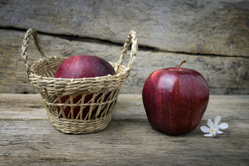 Basket with apples on grunge wooden background