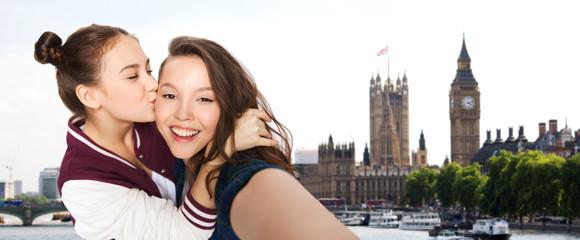 happy teenage girls taking selfie in london