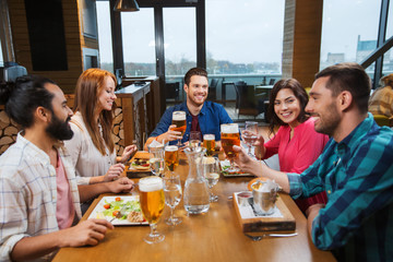 friends dining and drinking beer at restaurant