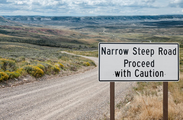 Narrow Steep Road Warning Sign:  A sign urges caution on a narrow gravel road in the mountains of southwest Wyoming.