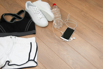 sport, fitness, healthy lifestyle and objects concept - close up of female sports clothing, sneakers, smartphone, earphones and bottle