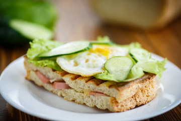 sandwich with sausage, cheese, lettuce and eggs