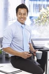 Happy businessman holding mobile and tea mug