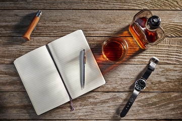 Overhead view of a notebook, whiskey, a knife, and a watch