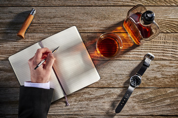 overhead view of a person writing in a notebook with whiskey on the table