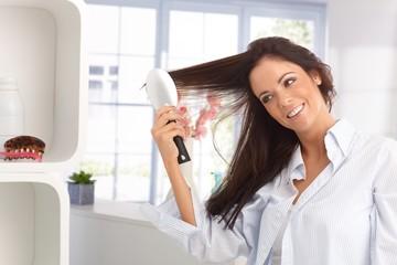 Happy woman combing hair