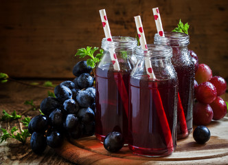 Dark grape juice in glass bottles with straws, blue grapes, dark