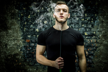 Young handsome man in black t-shirt smoking hookah with weathered brick wall on background