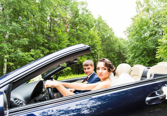 Beautiful young couple bride and groom posing in cabriolet