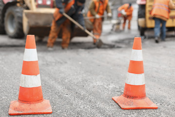 road workers repair the road,  cones in  foreground