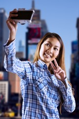 Composite image of smiling asian woman taking picture