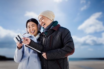Composite image of couple laughing at their pictures
