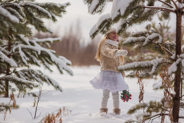 The girl was walking through the woods in the winter and the snow was falling on her