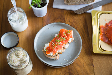Sandwich with smoked salmon, cottage cheese, garden cress and sesame seeds. Selective focus.