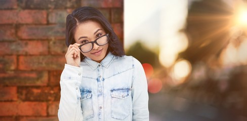 Composite image of asian woman holding eyeglasses