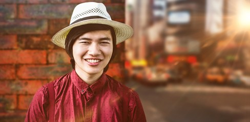 Composite image of smiling hipster with a straw hat