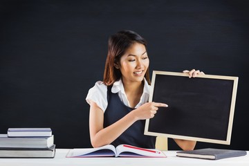 Composite image of smiling businesswoman pointing a blackboard