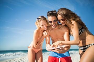 Happy friends taking selfie on the beach