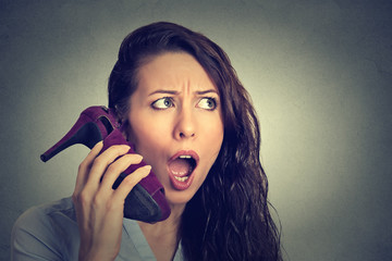 woman looking excited, surprised holding high heeled shoe in her hand as phone
