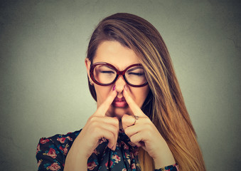 woman pinches nose with fingers looks with disgust bad smell