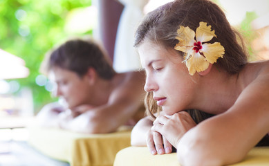 beautiful young woman and handsome young man enjoying their time in tropical spa