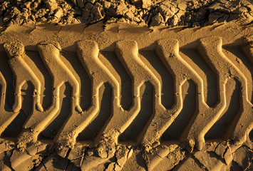 embossed trail excavator tracks on the sand. closeup texture of