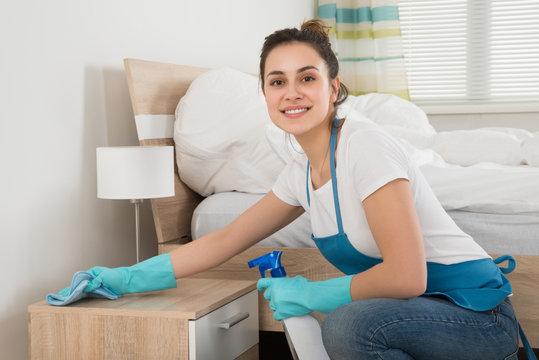 Female Housekeeper Cleaning Nightstand