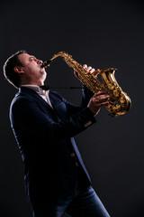 musician plays jazz at saxophone