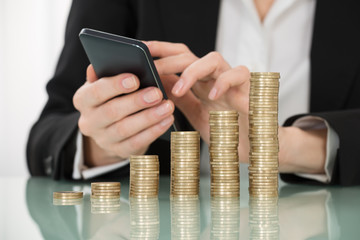 Businesswoman Using Smartphone With Stacked Coins On Desk