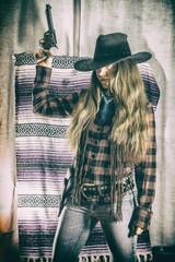 Cowgirl Gunslinger Standing Gun Up. Old west cowgirl gunslinger standing with peacemaker gun held up, edited in vintage film style.