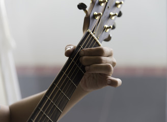 Unidentified male play guitar with left arm closeup