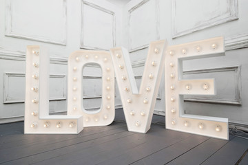 Custom made L O V E letters with light bulb in the corner of vintage room
