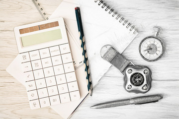 Compass, pocket watch, calculator, notepad, ruler, pen