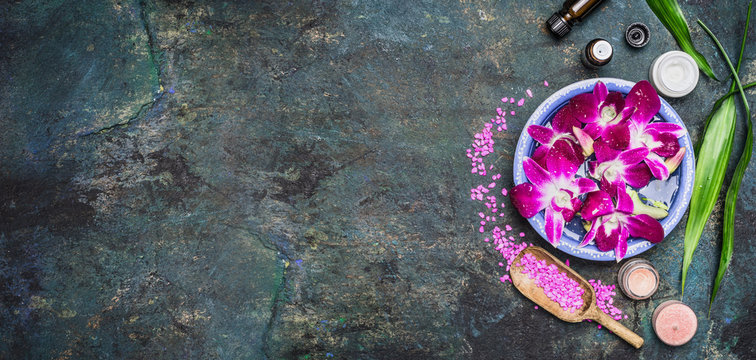 Spa setting with water bowls , pink orchid flowers ,sea salt, cosmetic cream and essential oil on dark rustic background , top view, place for text, horizontal, banner. Wellness concept