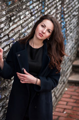 young beautiful girl with dark long hair in black coat standing outdoors near a wall