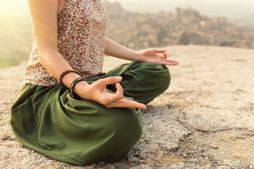 Young woman meditating at mountain cliff on sunrise. Hands close-up