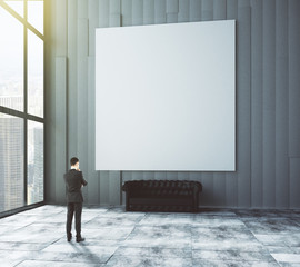 Businessman looks at blank poster on the wall in empty room with